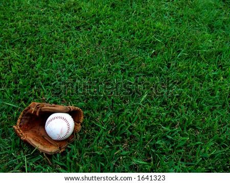 Softball glove and mitt on grass field. - stock photo