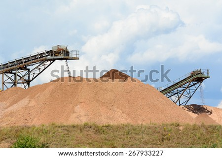 Soil and rocks being transported by conveyor belts at quarry - stock photo