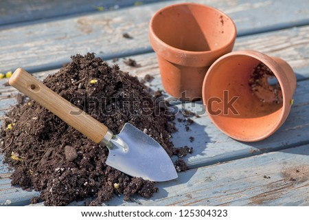 Soil and trowel to fill two empty clay pots. - stock photo