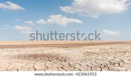 Soil drought cracked landscape on blue sky background - stock photo