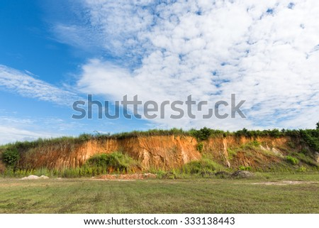Soil structure, Wall cliff - clay brown soil and grass, Soil cross section, green grass and blue sky - stock photo
