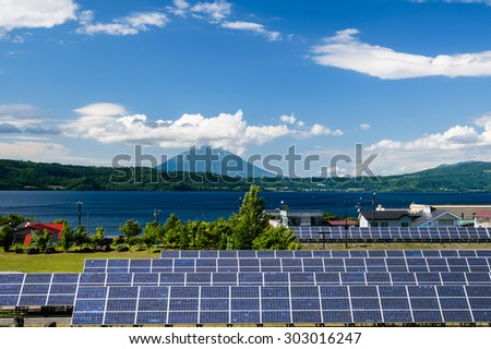 Solar cell panel and village in rural area with mountain landscape background - stock photo