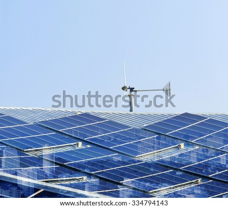 solar cell panel and wind turbines on factory roof with city screen eco concepts - stock photo