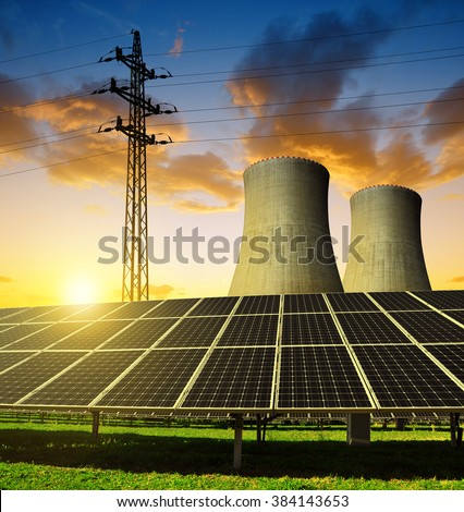 Solar energy panels, nuclear power plant and electricity pylon at sunset. - stock photo