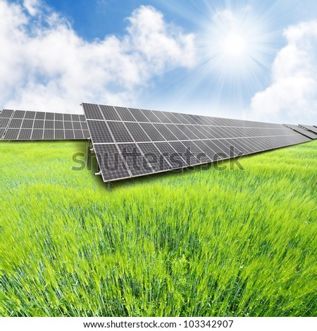 Solar energy panels on a green wheat field. Renewable energy concept. - stock photo