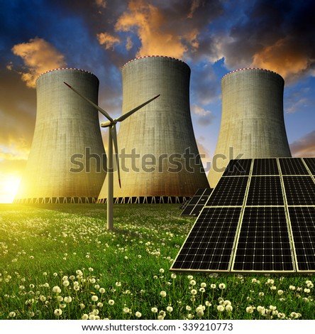 Solar energy panels, wind turbine and nuclear power plant at sunset. - stock photo