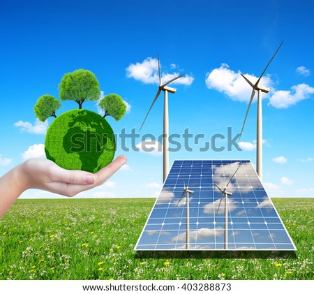 Solar energy panels with wind turbines and green planet in hand. Concept of environmental protection. - stock photo