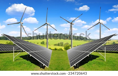 Solar energy panels with wind turbines in spring landscape - stock photo