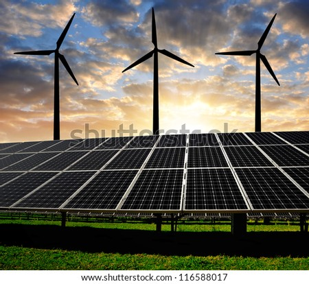 Solar energy panels with wind turbines in the sunset - stock photo