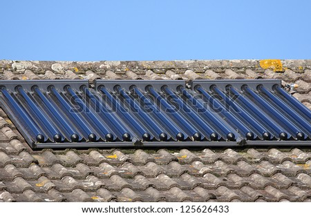 Solar glass tube hot water panel array mounted on a tiled roof - stock photo