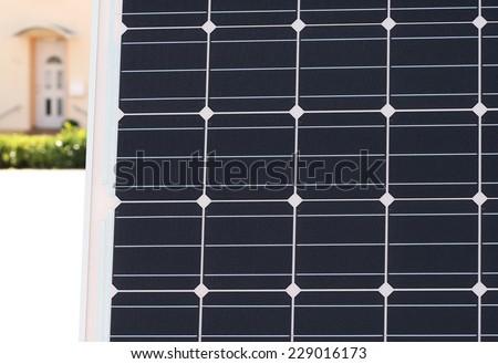 Solar Module with the Entrance of an Apartment House in the Background - stock photo