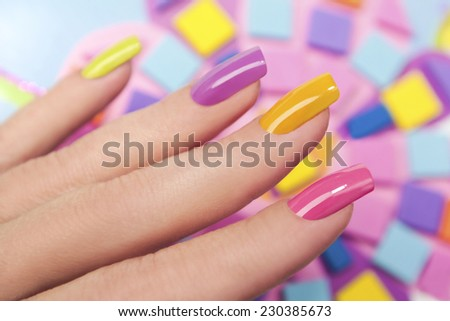 Solar nails are covered with multi-colored with colored lacquer on the female hand. - stock photo