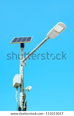 Solar panel cell powered street light lamp on a blue sky background - stock photo