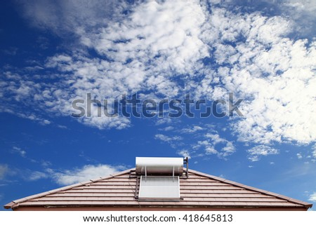 Solar panel for hot water system on roof on blue sky background - stock photo