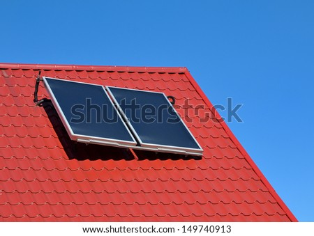 Solar panel on a red roof on blue sky - stock photo