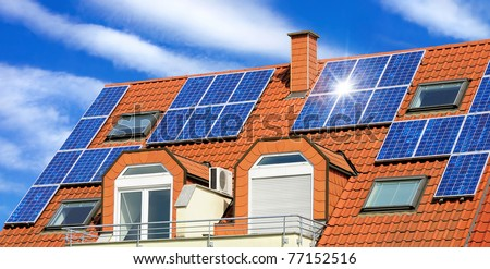 Solar panel on a red roof with white clouds and the reflection of the sun - stock photo