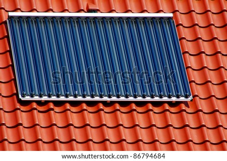 Solar panel on a red roofing tile - stock photo