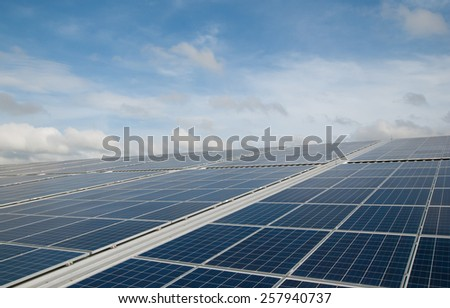 Solar panel on a roof reflecting the sun with cloudy background and blue sky - stock photo