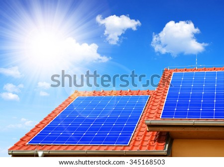 Solar panel on the roof of the house in the background sunny sky. - stock photo