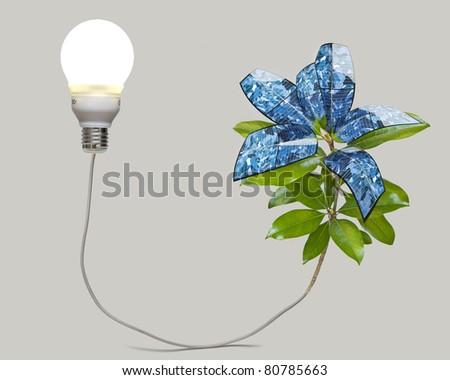 Solar panel plant illuminates an energy saving light bulb. Conceptual image of perpetual, clean energy. - stock photo