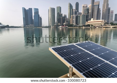 Solar panel with modern city and skyscrapers on background - stock photo