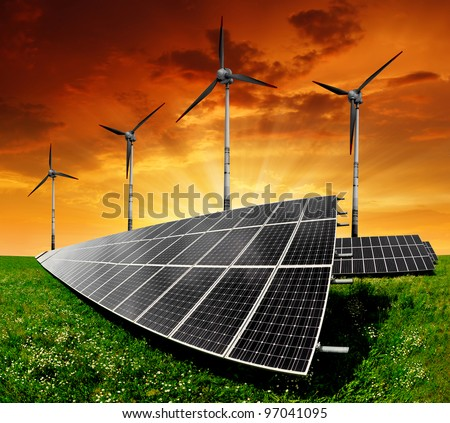 Solar panels and wind turbine in the setting sun - stock photo