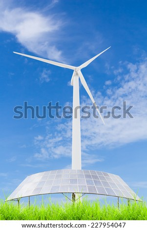 Solar panels and wind turbine on green grass field against blue sky background,useful for carbon credits concept. - stock photo