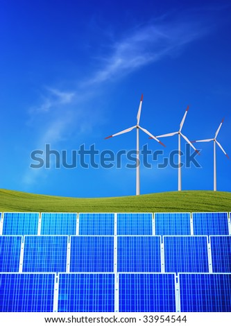 Solar panels and wind turbines against green field and blue sky - stock photo