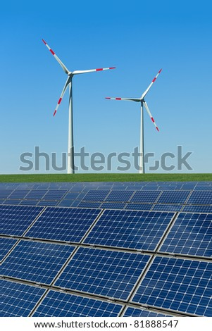 Solar panels and wind turbines in a field - stock photo