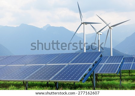 solar panels and wind turbines on summer landscape with mountains on background - stock photo