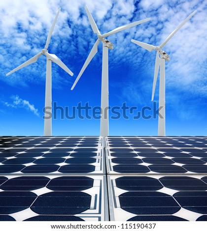 Solar panels and Wind Turbines under cloudy blue sky - stock photo