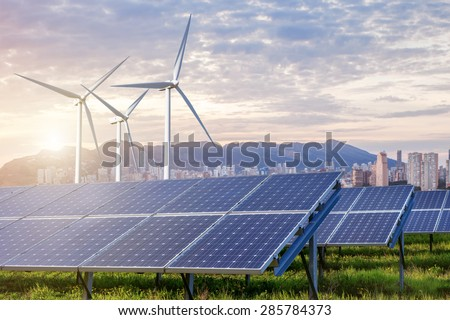 solar panels and wind turbines under sky and clouds with city on horizon. Sunrise - stock photo