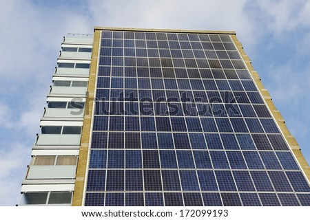 Solar panels attached on the wall of an old apartment building - stock photo