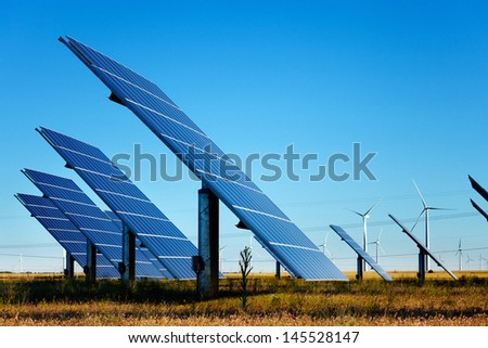 Solar panels farm and wind turbines at background under a blue sky.  - stock photo