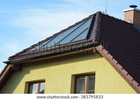 Solar panels for water heating installed on the roof of family house - stock photo