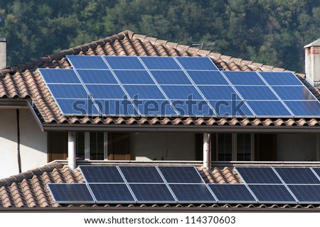 solar panels in a house roof - stock photo