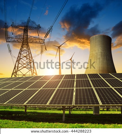 Solar panels in the background nuclear power plant, wind turbines and electricity pylon at sunset. Concept of energy resources. - stock photo