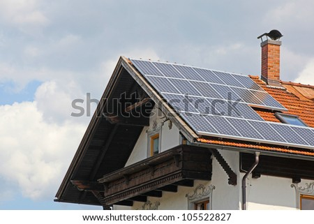 Solar panels on the roof of te small house - stock photo