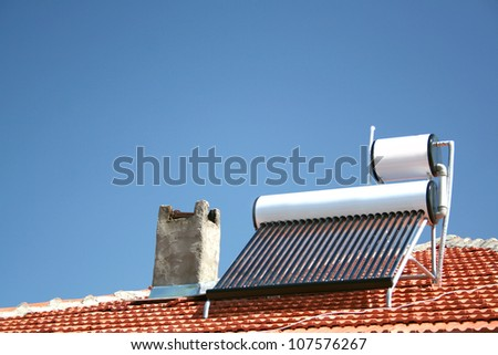 solar panels with water collector on the roof of house - stock photo