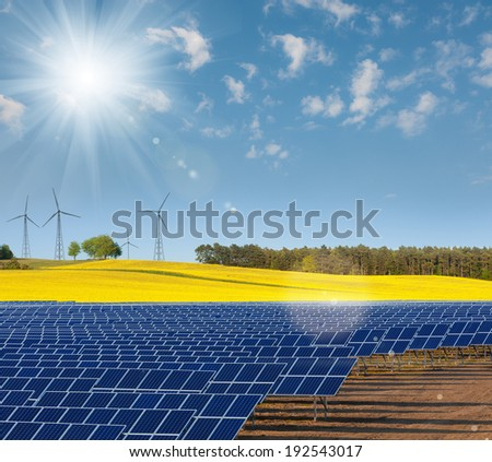 Solar power cells, rapeseed field and windmills on the horizon - stock photo