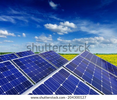 Solar power generation technology, green alternative energy and environment protection ecology business concept background -  solar battery panels in blooming rural meadow field with blue sky - stock photo