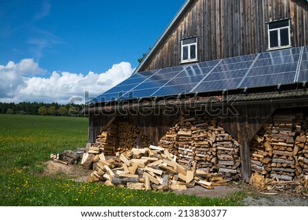 solar power panels on barn roof with stacked fire wood in front - stock photo