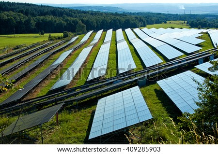 Solar power plant on a greenfield site between forests. The Smoking smokestack and the industrial landscape fading into the mist in the background. View from above. - stock photo