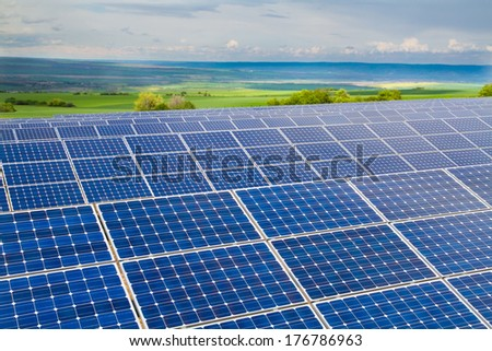 Solar power plant on the background of green fields - stock photo