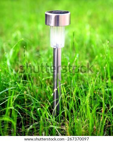 Solar Powered Outdoor Garden Lamp on the Grass - stock photo