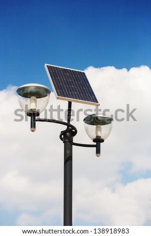Solar powered street lights, cloudy sky background - stock photo