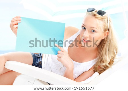 Solar promotion, holiday offer  Beautiful blonde woman sitting on a lounger beach holding a blue sign with space for text.  - stock photo