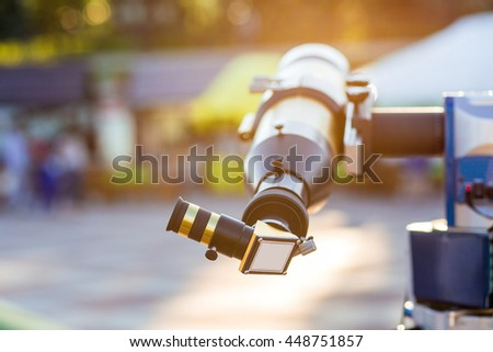 Solar telescope with a special filter to reduce sunlight standing outdoor in city park. Sun flare effect - stock photo
