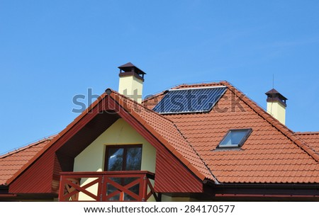 Solar water panel heating on new house roof against blue sky - stock photo