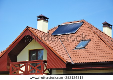 Solar water panel heating on red tiled house roof with lightning protection and chimney against blue sky - stock photo